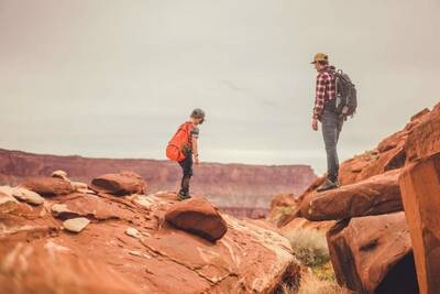 kid and dad in the desert; both wearing backpacks with outdoor gear for kids